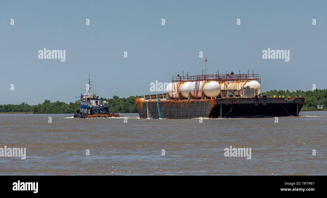 Pointe à la Hache, Louisiana - The Pacific Dawn tugboat pulls the Sea Crest liquid tank barge on the Mississippi River below New Orleans. - Stock Image