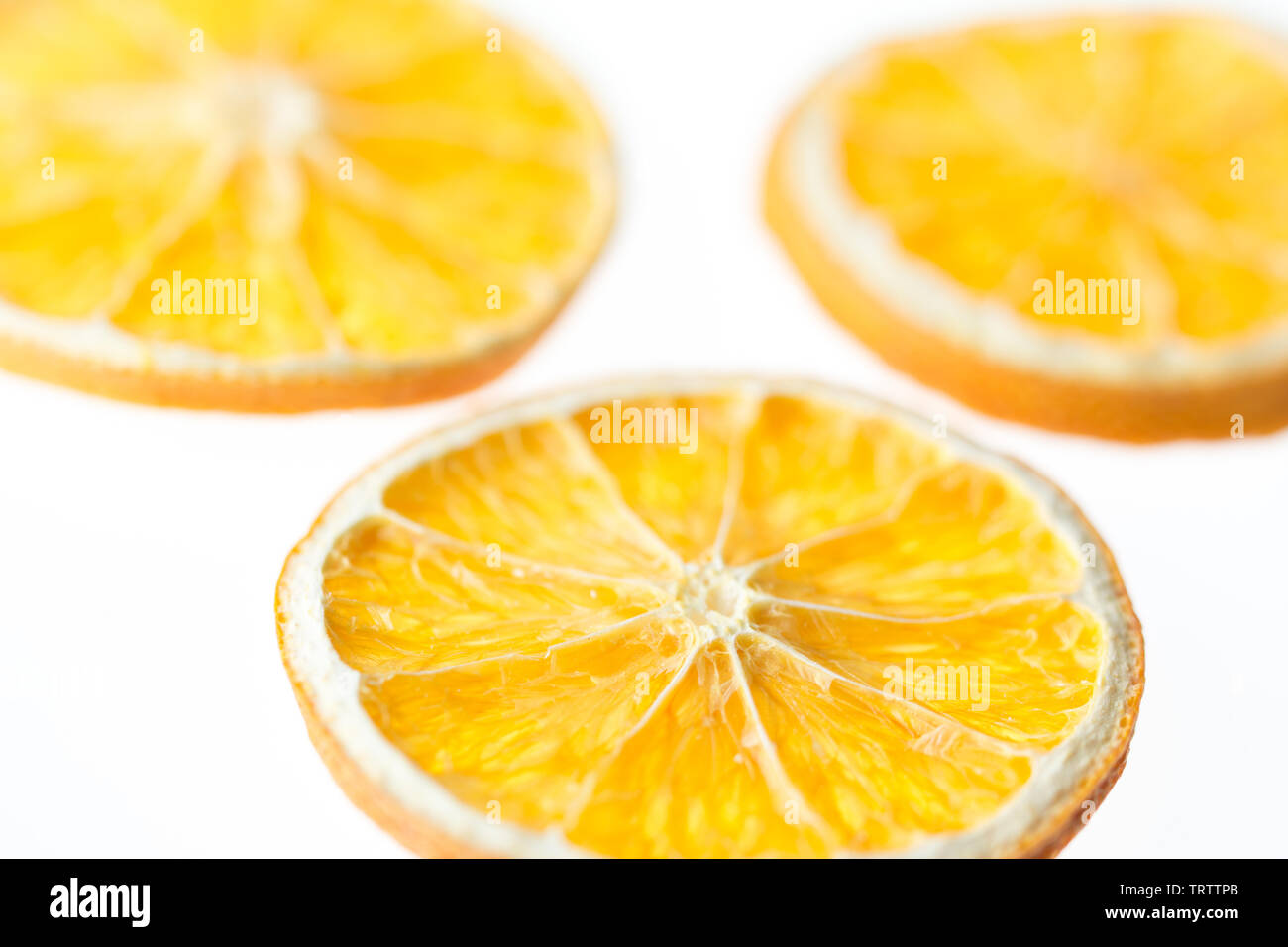 Three dried orange slices isolated on white background - selective focus - Stock Image
