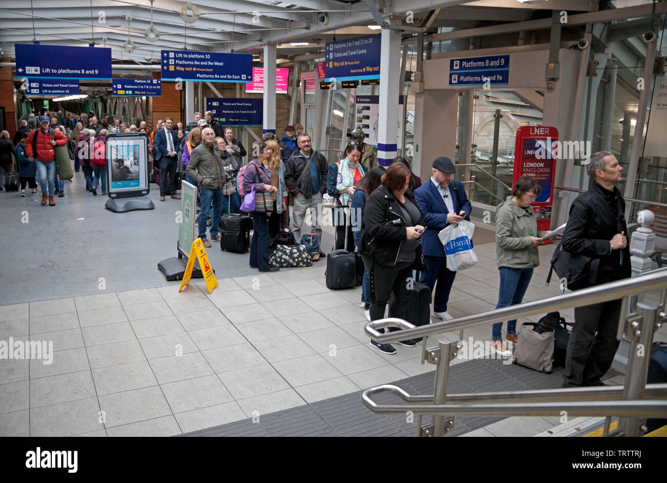 Edinburgh, UK. 12th June, 2019. Long queues of very frustrated passengers awaiting alternative transport by bus due to damage to the overhead wires between Carlisle and Lockerbie stations, all lines are blocked, Virgin Twitter feed warns 'services will be delayed as a result. Passengers require to check for updates to your journeys/services' Credit: Arch White/Alamy Live News - Stock Image