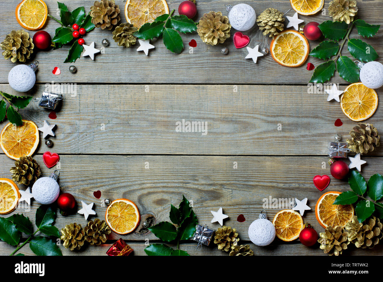 Christmas composition with orange slices, cones, holy, stars, small gift boxes, red and white baubles and hearts on wooden background - Stock Image