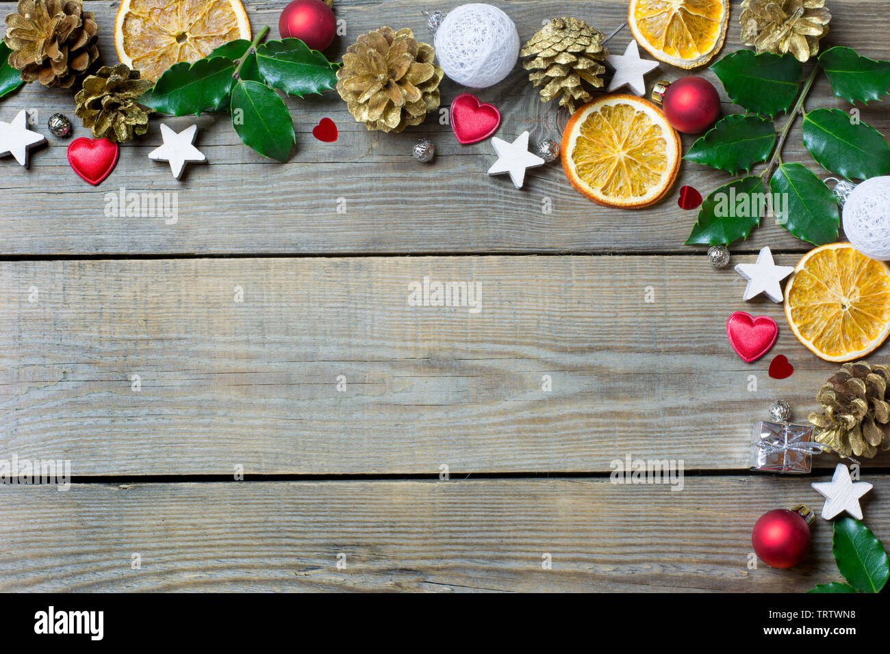 Christmas composition with orange slices, cones, holy, stars, small gift boxe, red and white baubles and hearts on wooden background - Stock Image