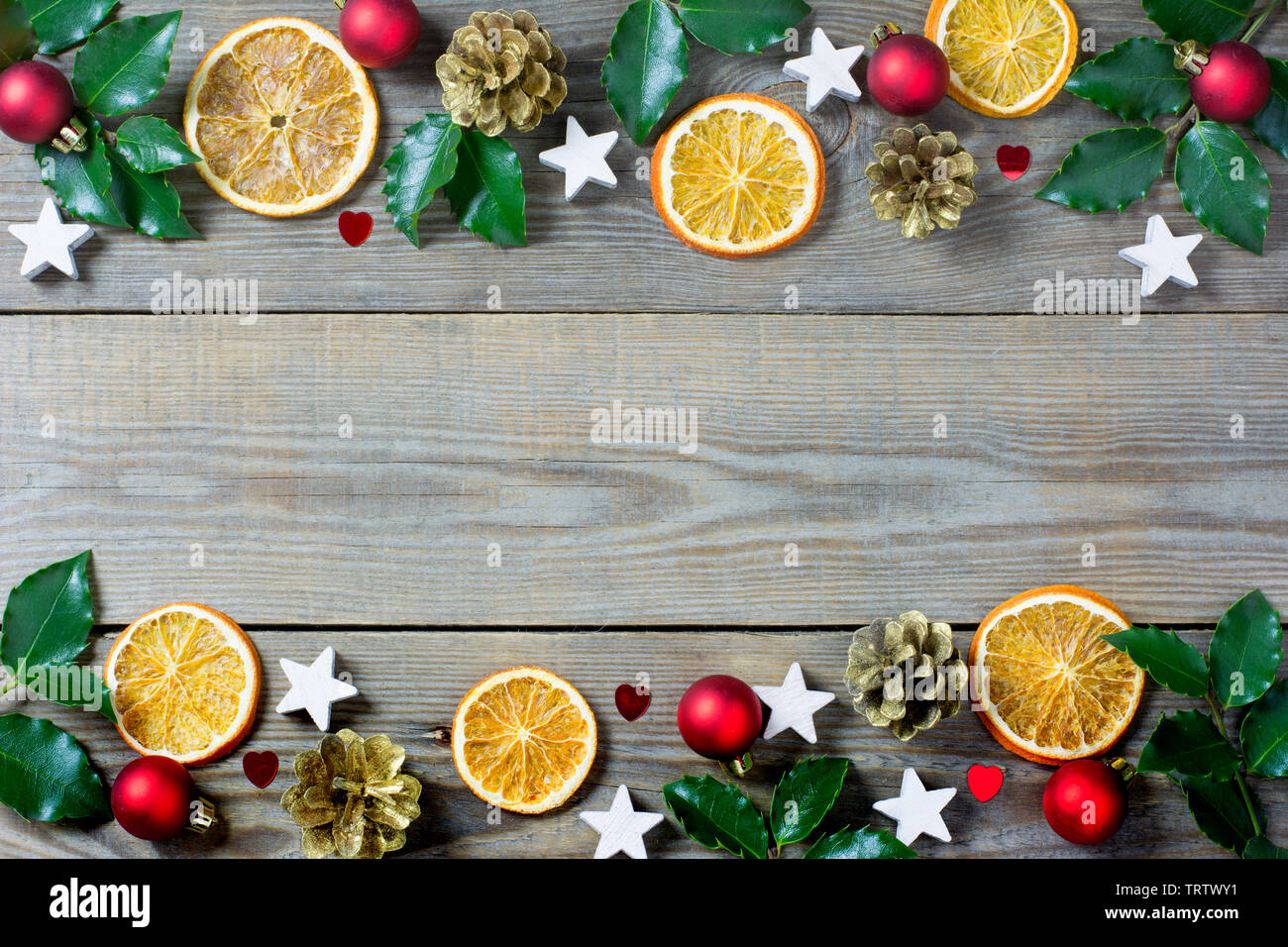 Christmas composition with orange slices, cones, holy, stars, red baubles and small  hearts on wooden background - Stock Image