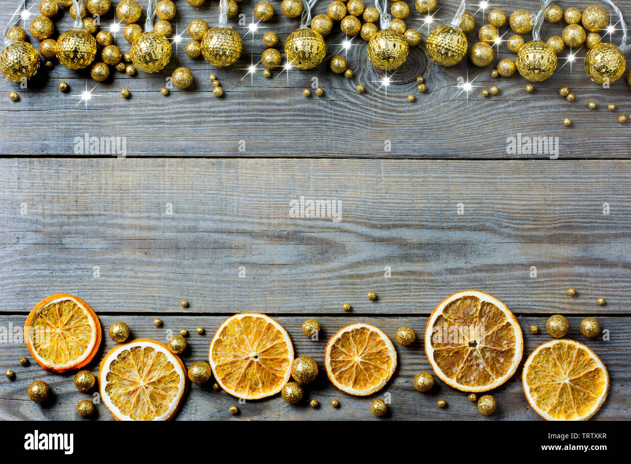 Christmas composition with orange slices, golden lights, golden glitter balls and white stars on wooden background - place for text - Stock Image