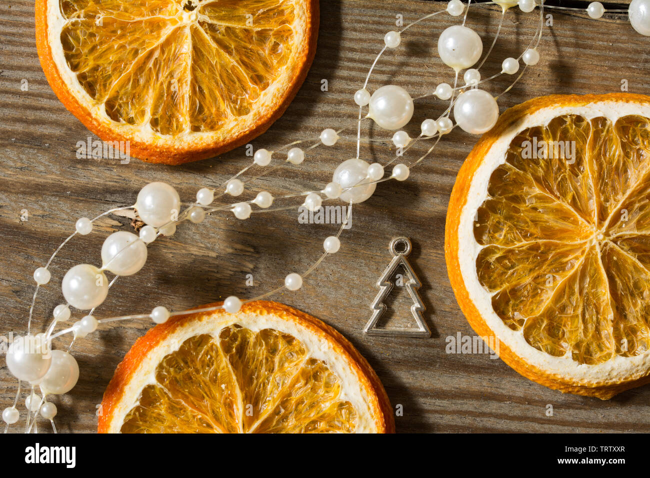 Christmas composition with dried oranges, white bead chain and silver christmas tree shape on wooden background - close-up - Stock Image