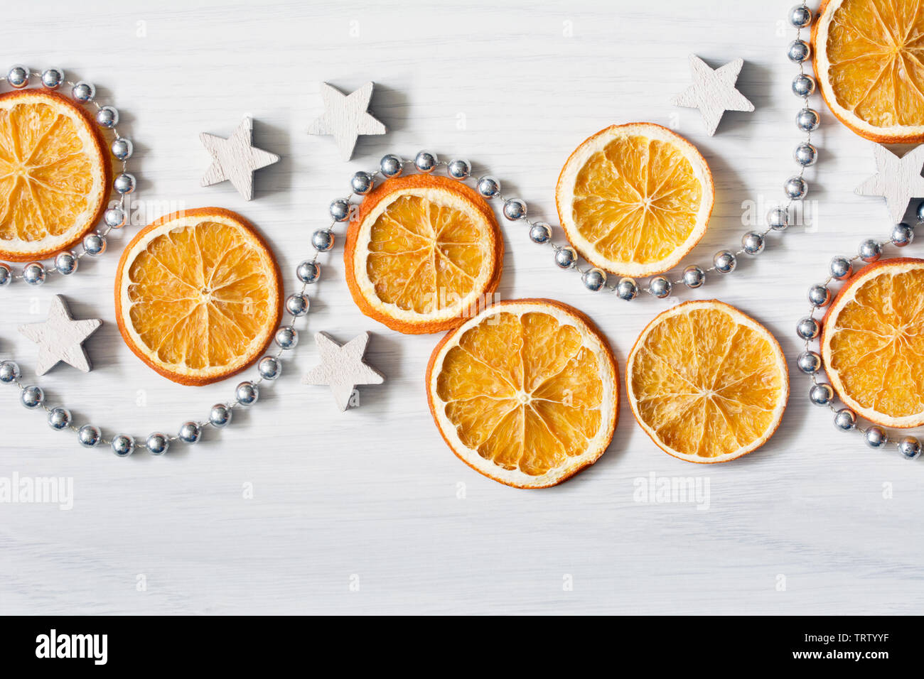 Christmas composition with dried oranges, white stars and silver bead chain - white background with deep shadows - close-up - Stock Image