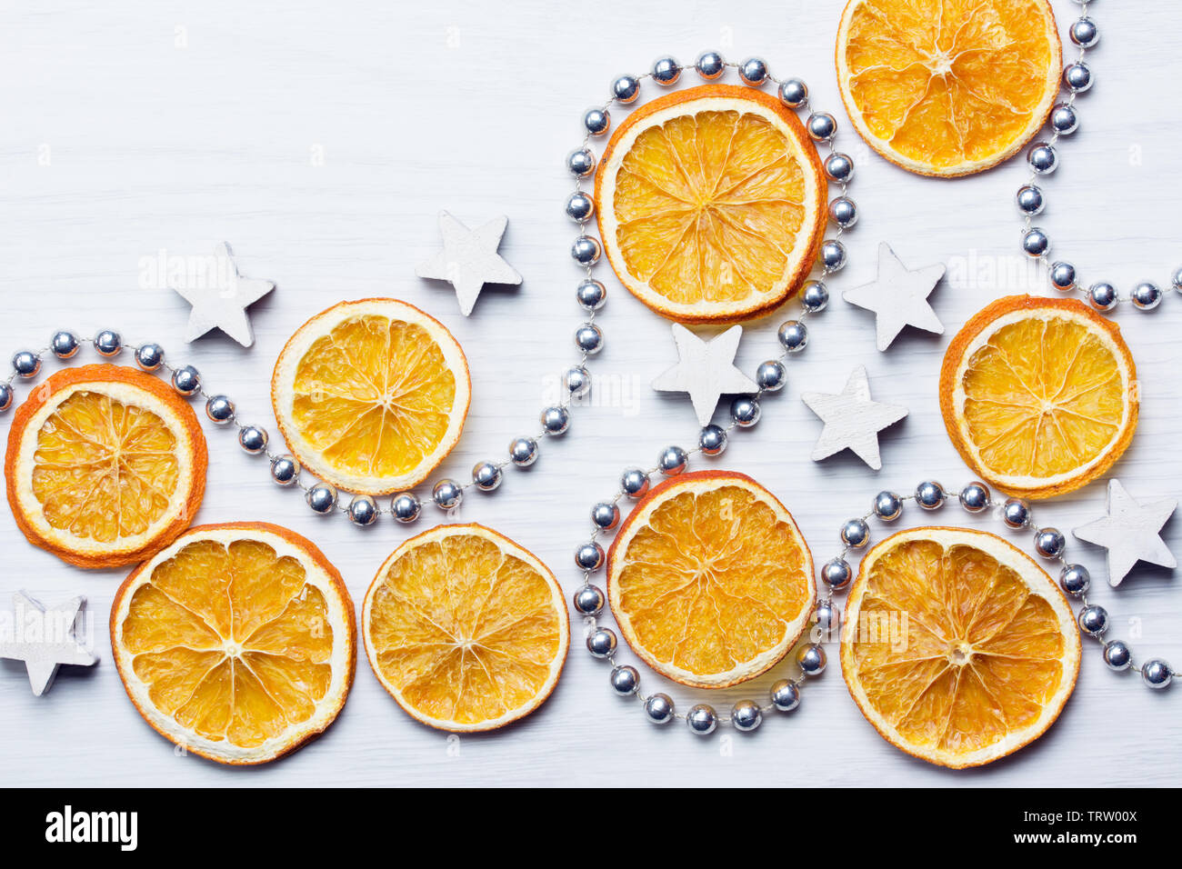 Christmas composition with dried oranges, white stars and silver bead chain - white background - close-up - Stock Image