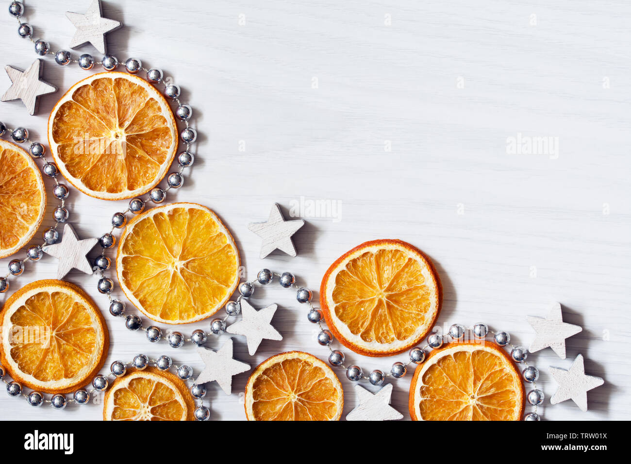 Christmas composition with dried oranges, white stars and silver bead chain - white background with deep shadows - close-up, text space - Stock Image