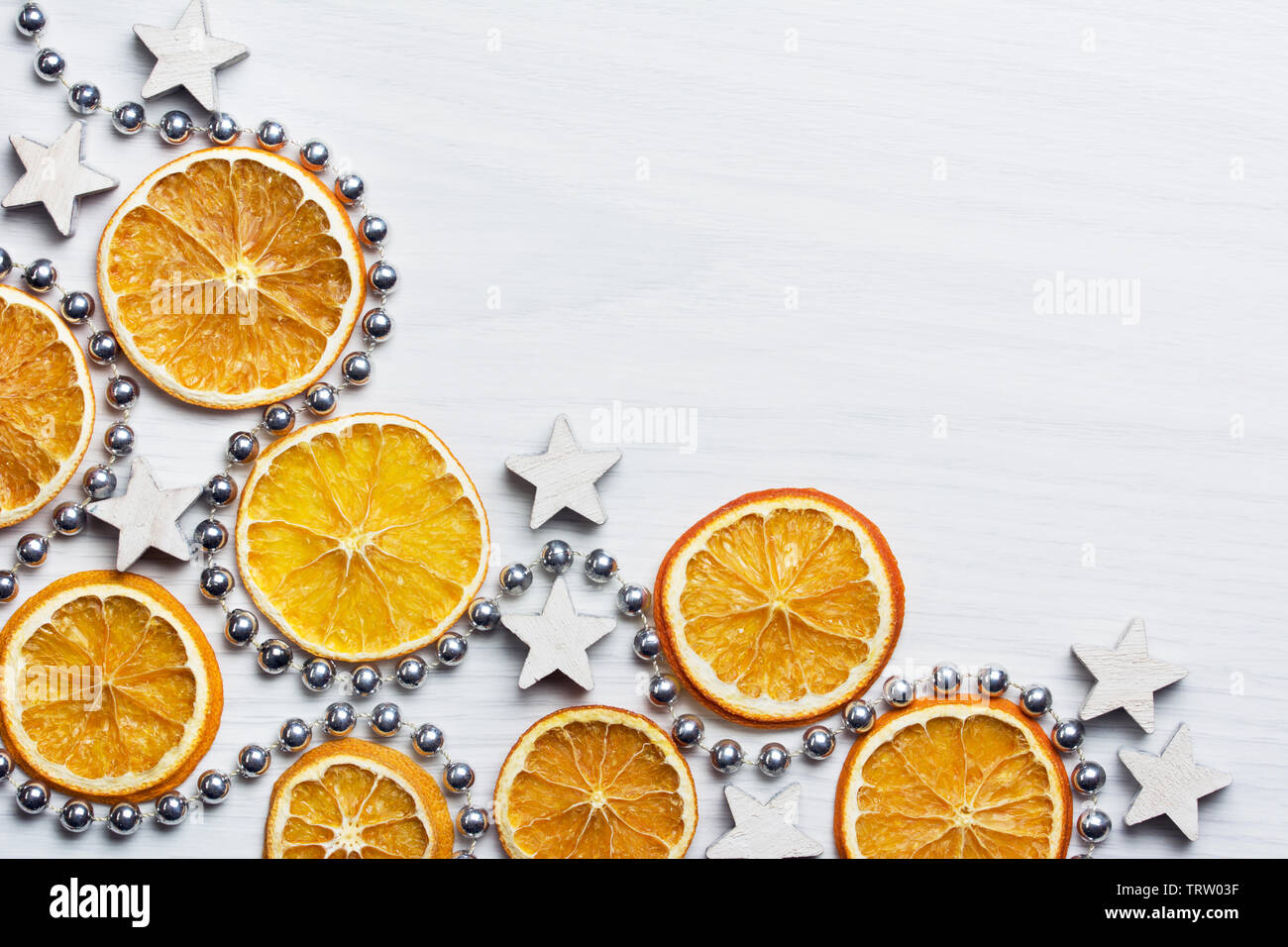 Christmas composition with dried oranges, white stars and silver bead chain - white background - close-up, text space - Stock Image