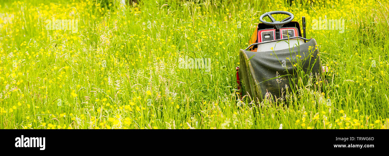 A forgotten and abandoned lawn mower left in long grass in a field. - Stock Image