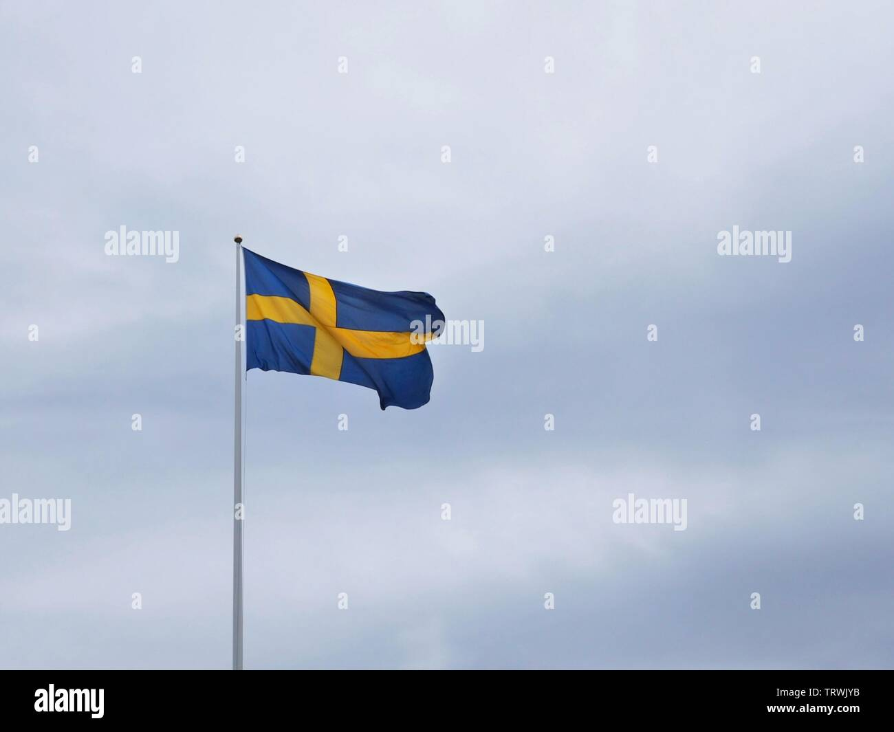 The swedish flag waving in the wind in a grey cloudy sky. - Stock Image