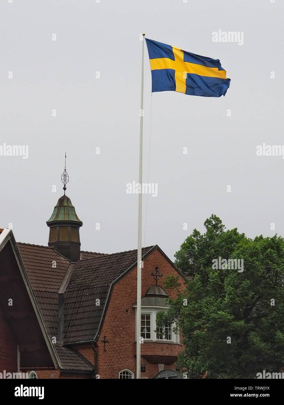 The swedish flag in front of an old building - Stock Image