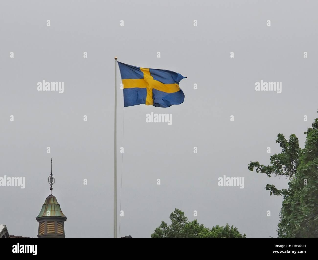 The swedish flag in a grey cloudy sky - Stock Image