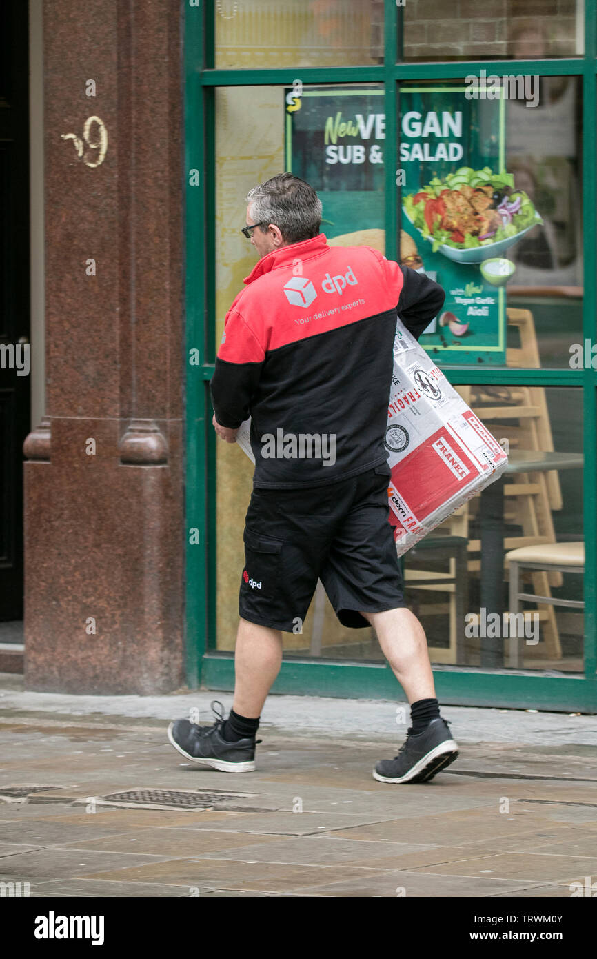 a DPD parcel courier delivery parcels to customers in Manchester city centre - Stock Image