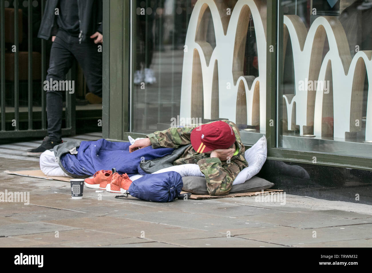 A homeless person sat on the cold streets of Manchester city centre, UK - Stock Image