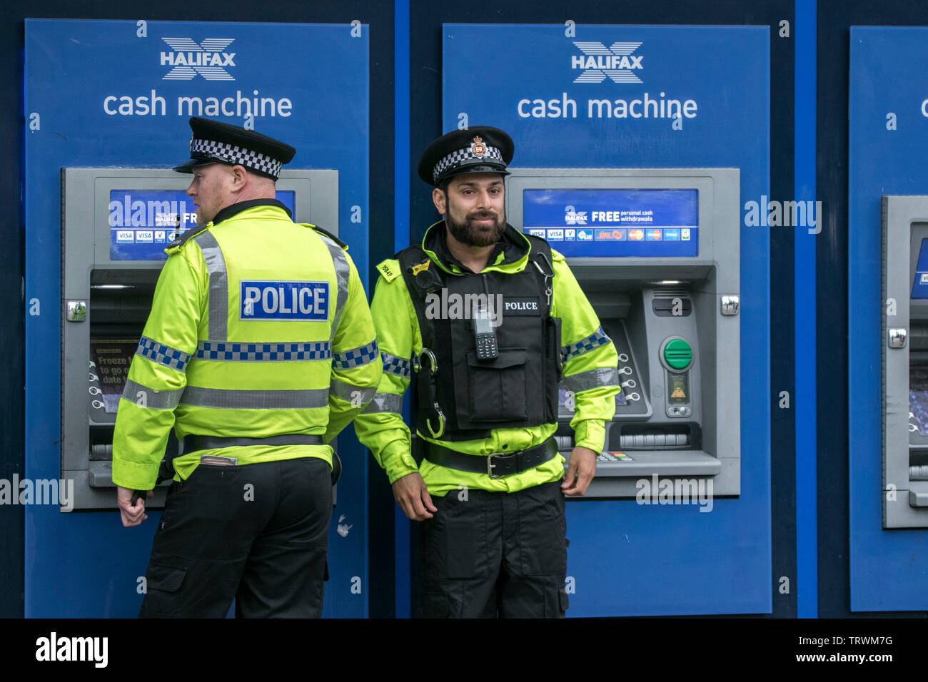 Two police officers at cash machine in Manchester city centre - Stock Image