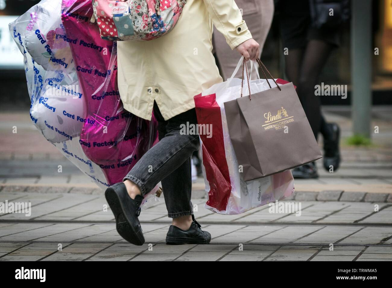 A woman carries multiple carrier bags after a shopping trip through the streets of Manchester, UK Stock Photo