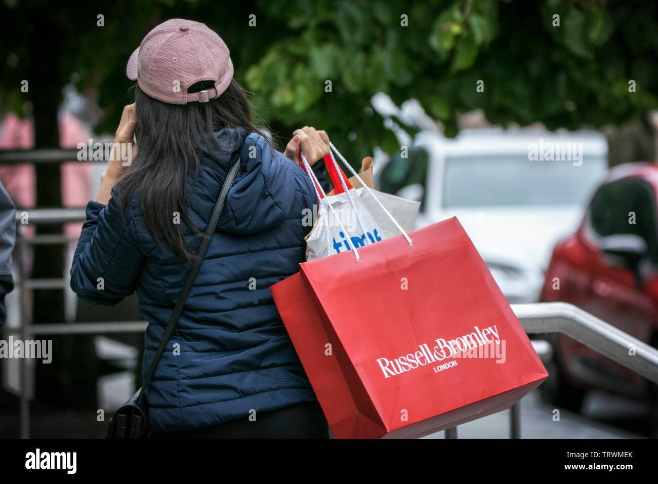 A woman carries a Russell and Bromley shoe store bag over her shoulder in Manchester city centre, UK - Stock Image