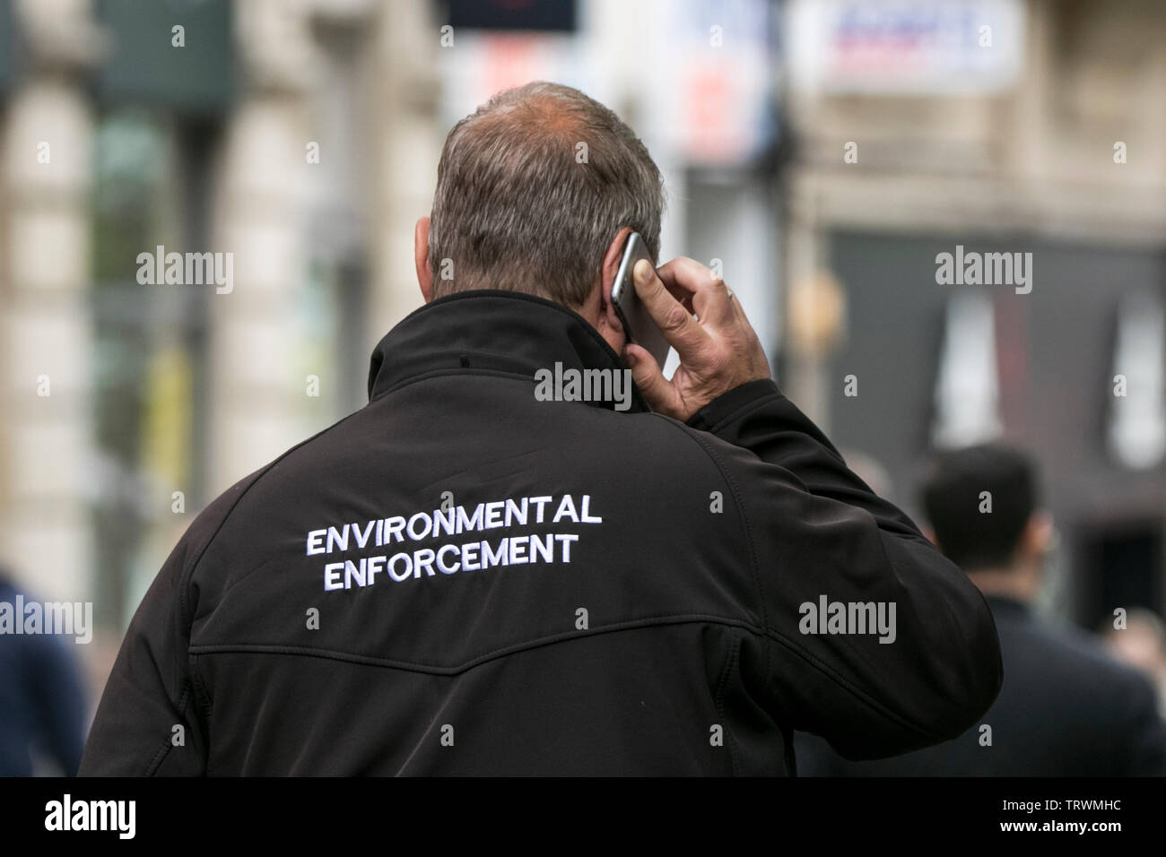 A civil enforcement officer patrols the city centre looking for littering offenders on the streets of Manchester, UK - Stock Image