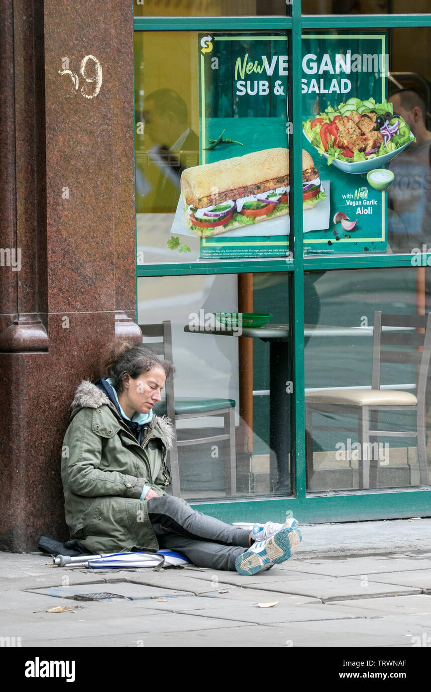 A homeless woman sleeps on the cold streets of Manchester city centre, UK - Stock Image