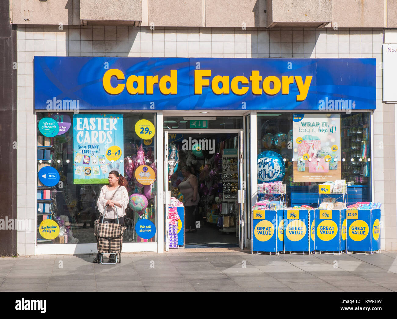 Shop front of Card Factory shop that sells cards for every occasion and a lady with a shopping trolley standing outside - Stock Image
