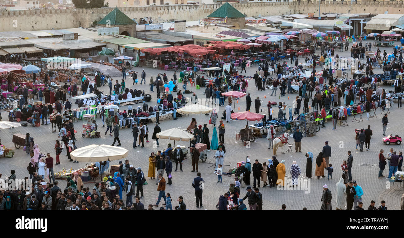 Wide angle view of El Hedim Square with restaurants, bars, countless market stalls and crowded with people and hawkers in the evening. Meknes, Morocco Stock Photo