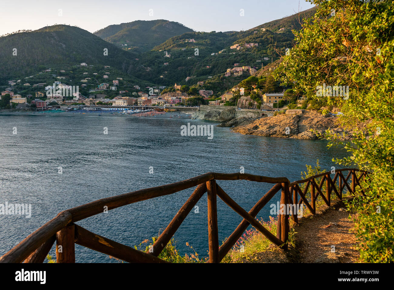 Mountain path, wooden fence on the side of  the mountain leading to the Mediterranean sea. In the distance, the beach of Bonassola, Liguria, - Stock Image