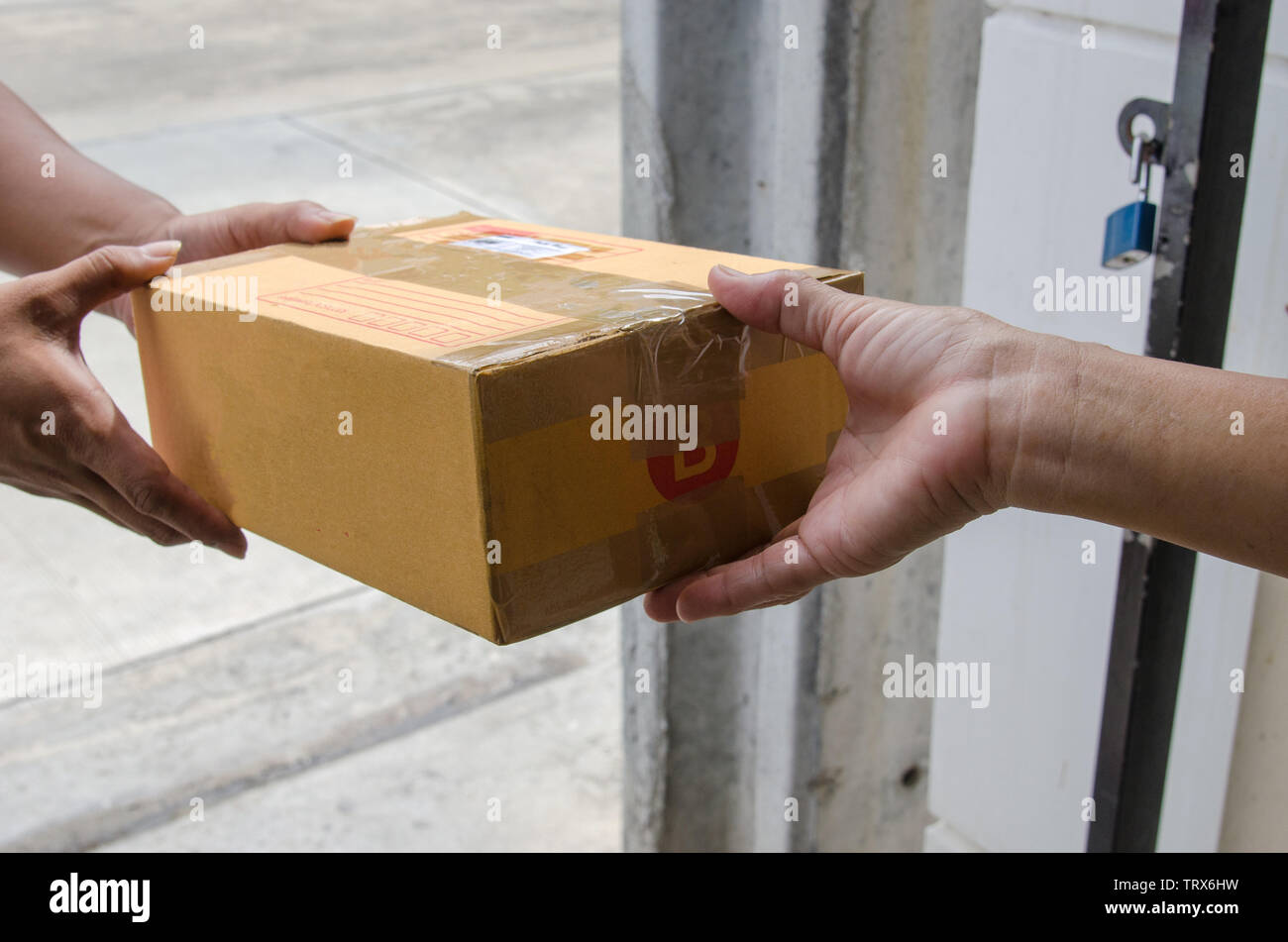 Men sent a parcel box at the front of the house, received by women. - Stock Image