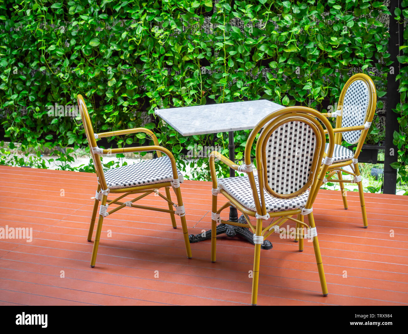 Three Wooden White Vintage Chairs With White Marble Table On Red Floor On Green Ivy Plant Background Dining Table Set In The Garden Stock Photo Alamy