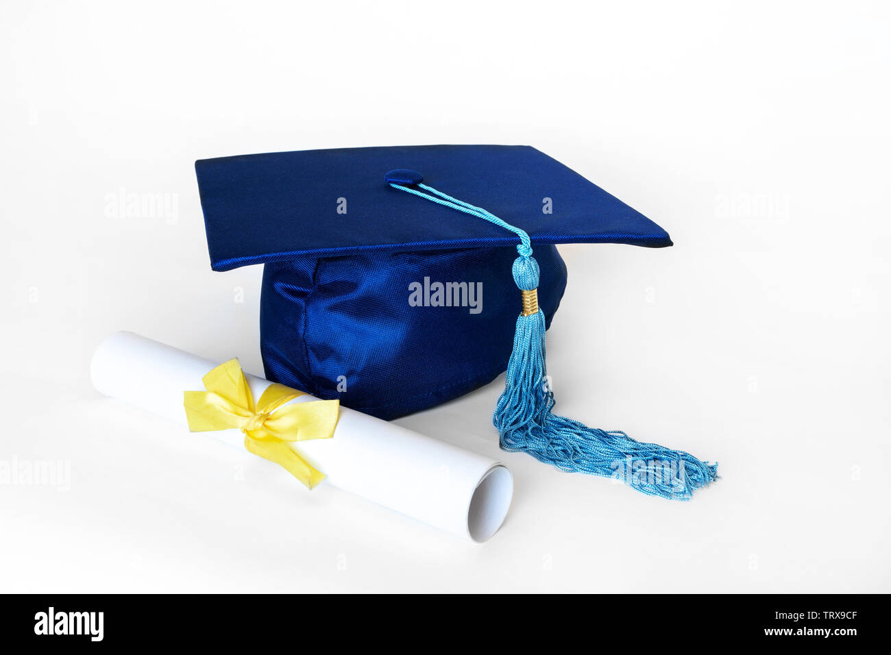 Blue graduation cap or mortarboard with blue tassel and diploma with yellow ribbon, isolated on white background. - Stock Image
