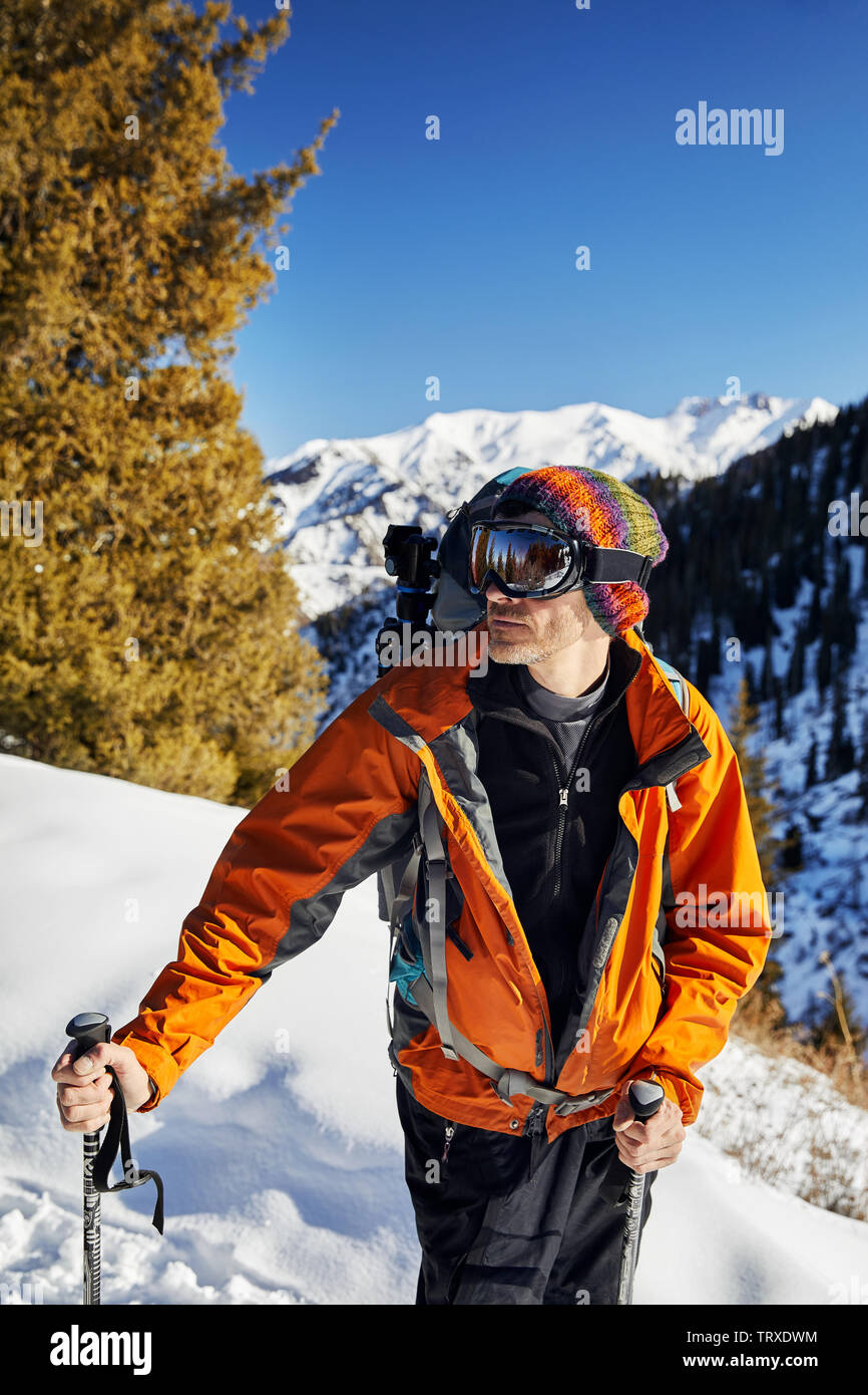 Portrait of skier in orange jacket and mask at snow mountain background at sunny day Stock Photo