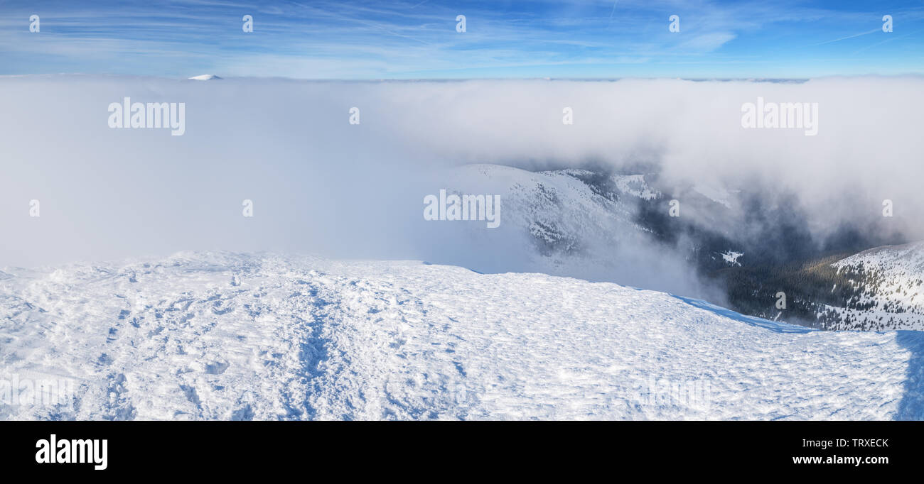 Mountain tops covered with snow above the white heavy clouds. - Stock Image