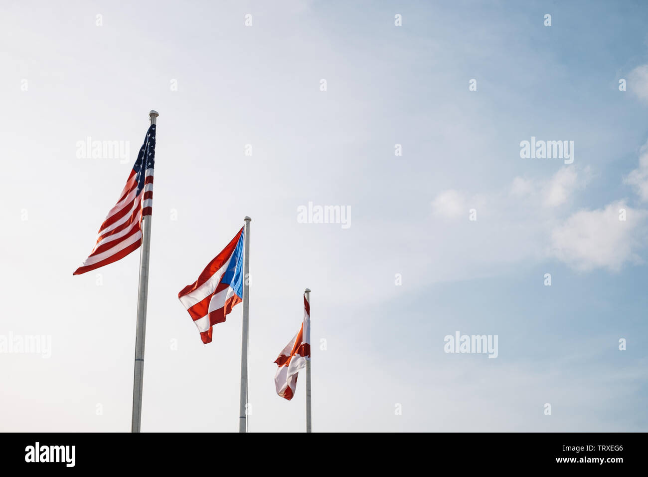 United States, Puerto Rico, and San Juan flags fly together above San Juan at sunset in Puerto Rico - Stock Image
