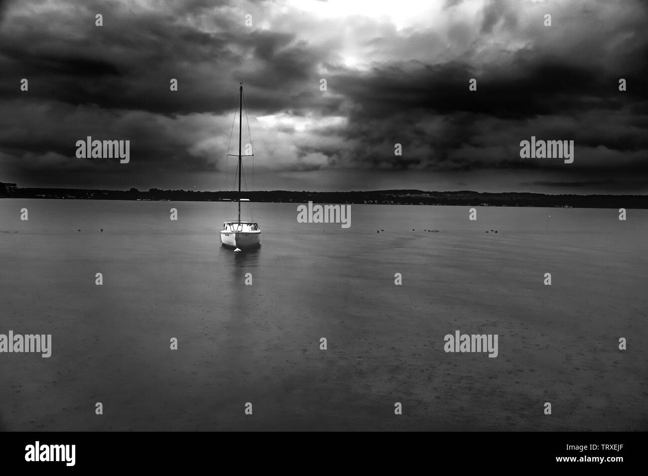 little sailboat floating under ominous stormy skies as it starts to rain. Stock Photo