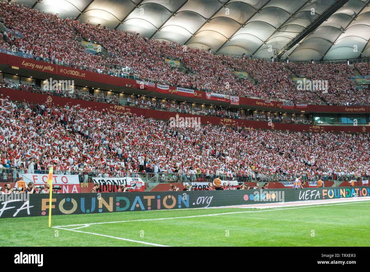 WARSAW, POLAND - JUNE 10, 2019: Qualifications Euro 2020  match Poland - Israel 4:0. Supporters of Poland with the small national flags. - Stock Image