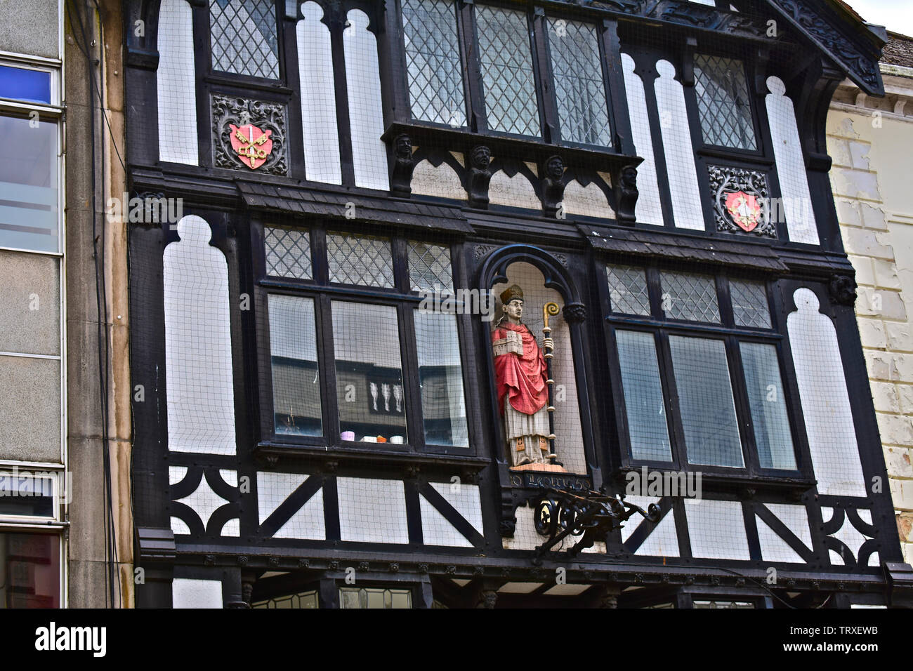 High Street, Exeter City Centre. Old half-timbered building occupied by Santander bank. Close-up detail of ornate carved figure at 2nd floor level. - Stock Image