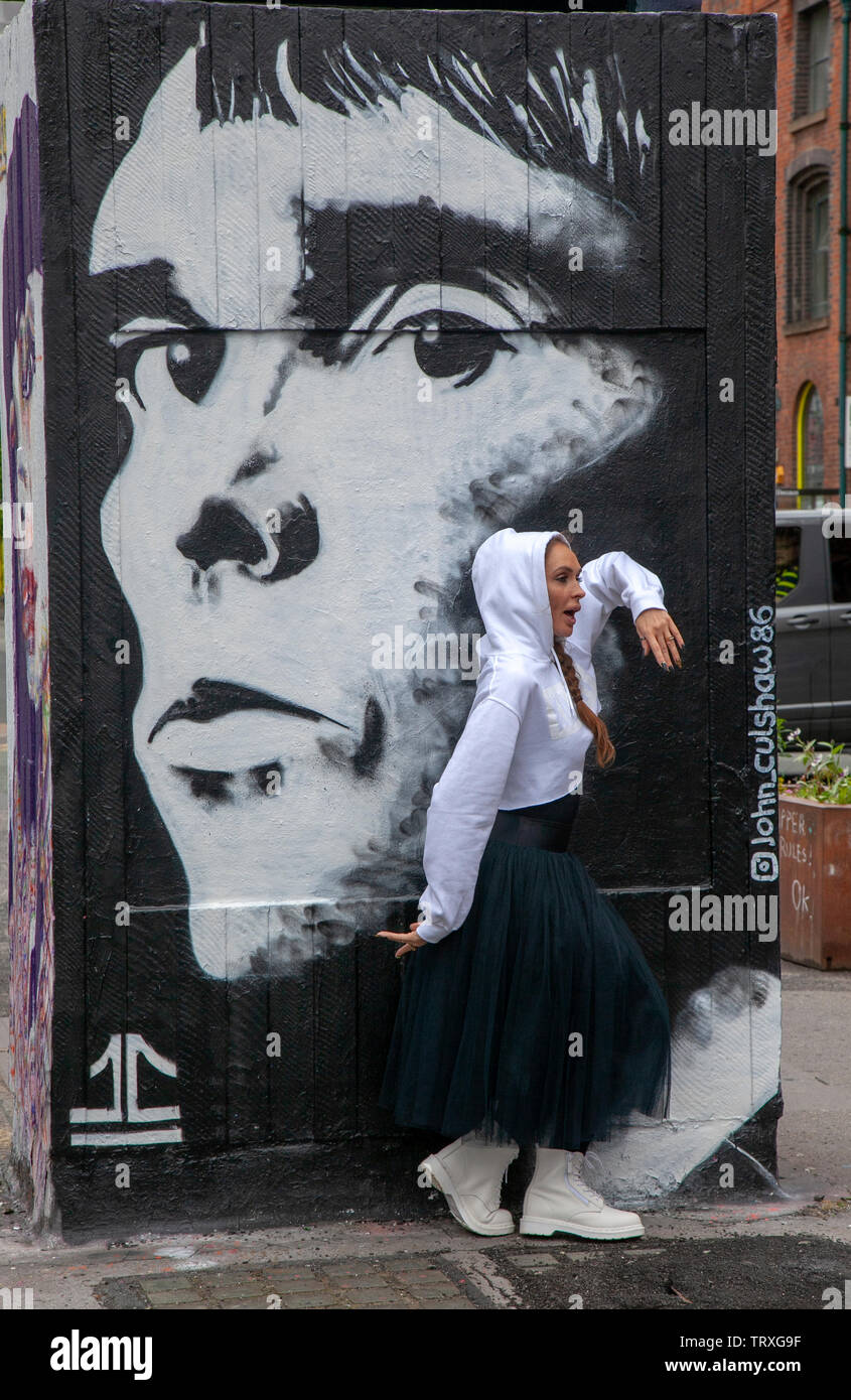 Dancer and an Ian Brown mural painted at Stevenson Square, the latest addition to the Outhouse MCR public art project. - Stock Image