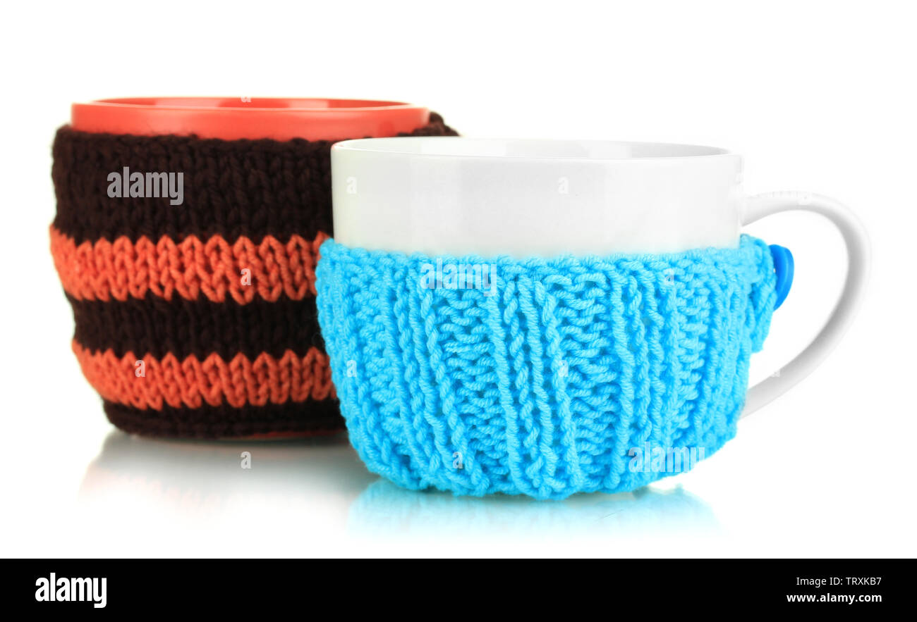 Cups with knitted things on it isolated on white Stock Photo
