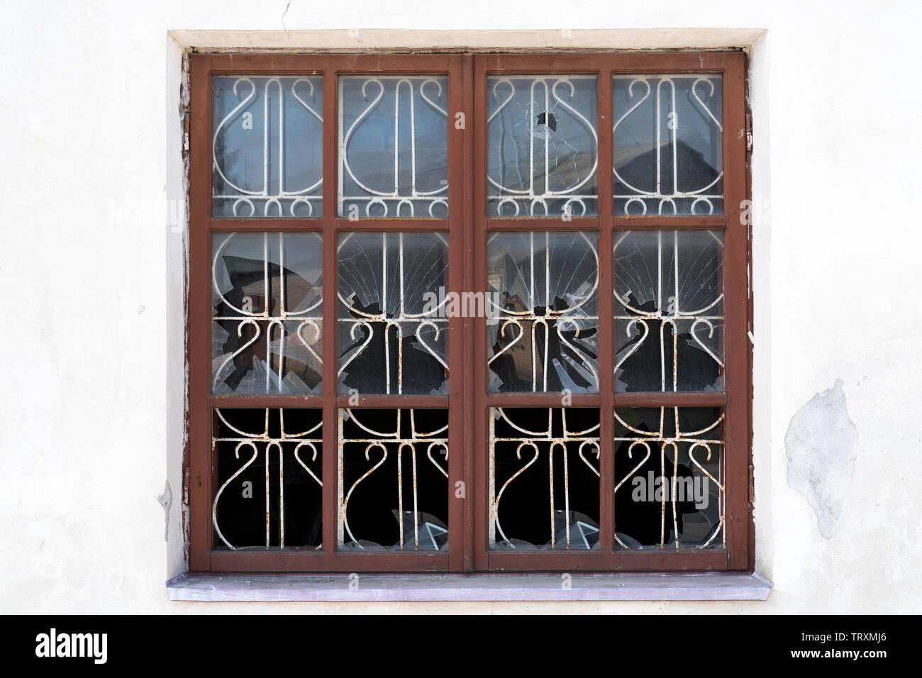 Broken barred window in an abandoned house. Vandalism,hooliganism concept. - Stock Image