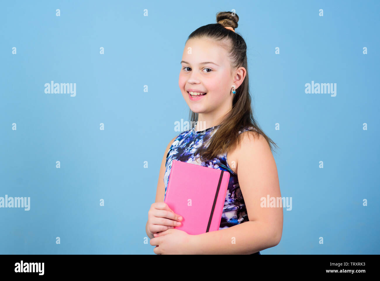 small girl with pink note book. school child with notepad. Smart and adorable. schoolgirl ready for lesson. school diaries for making note. love reading book. workbooks for writing. student read book. - Stock Image
