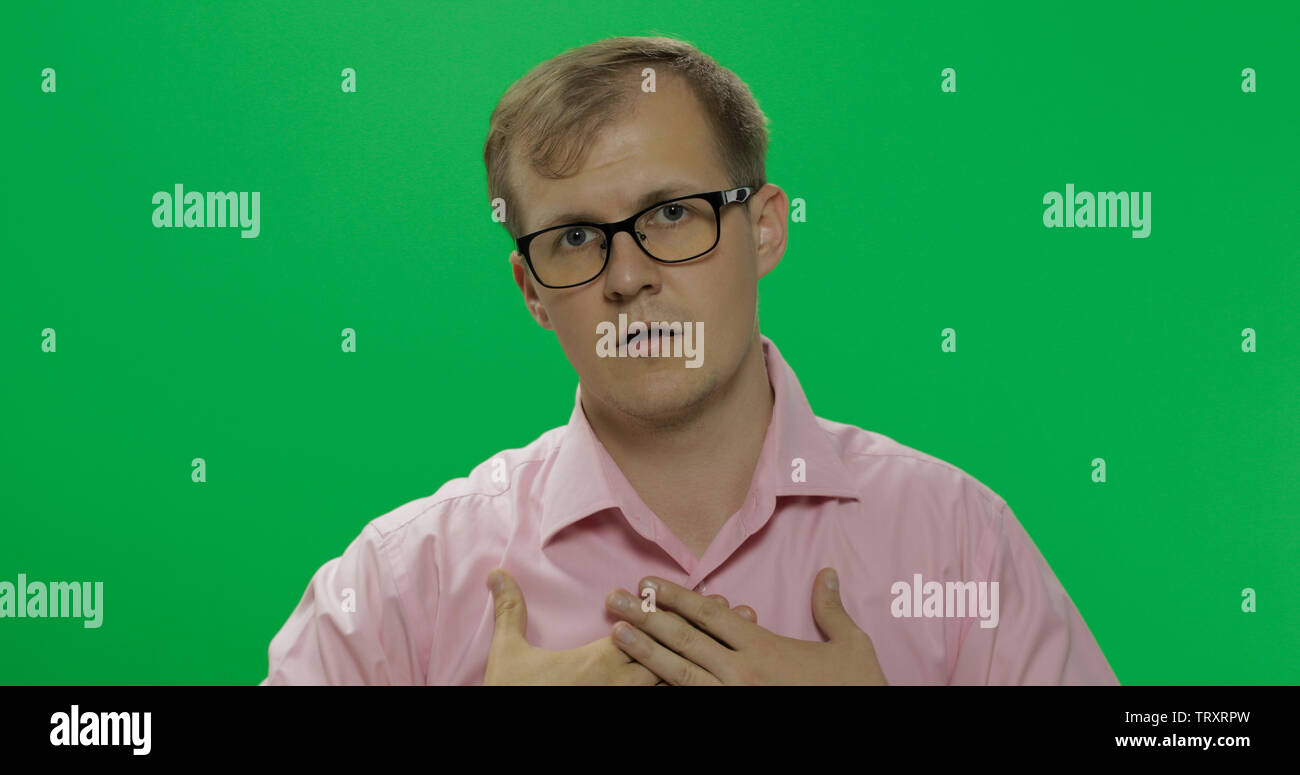 Portrait of the shy handsome young man in pink shirt trying to pay attention to him while standing in front of the camera on the green screen background. Chroma key - Stock Image