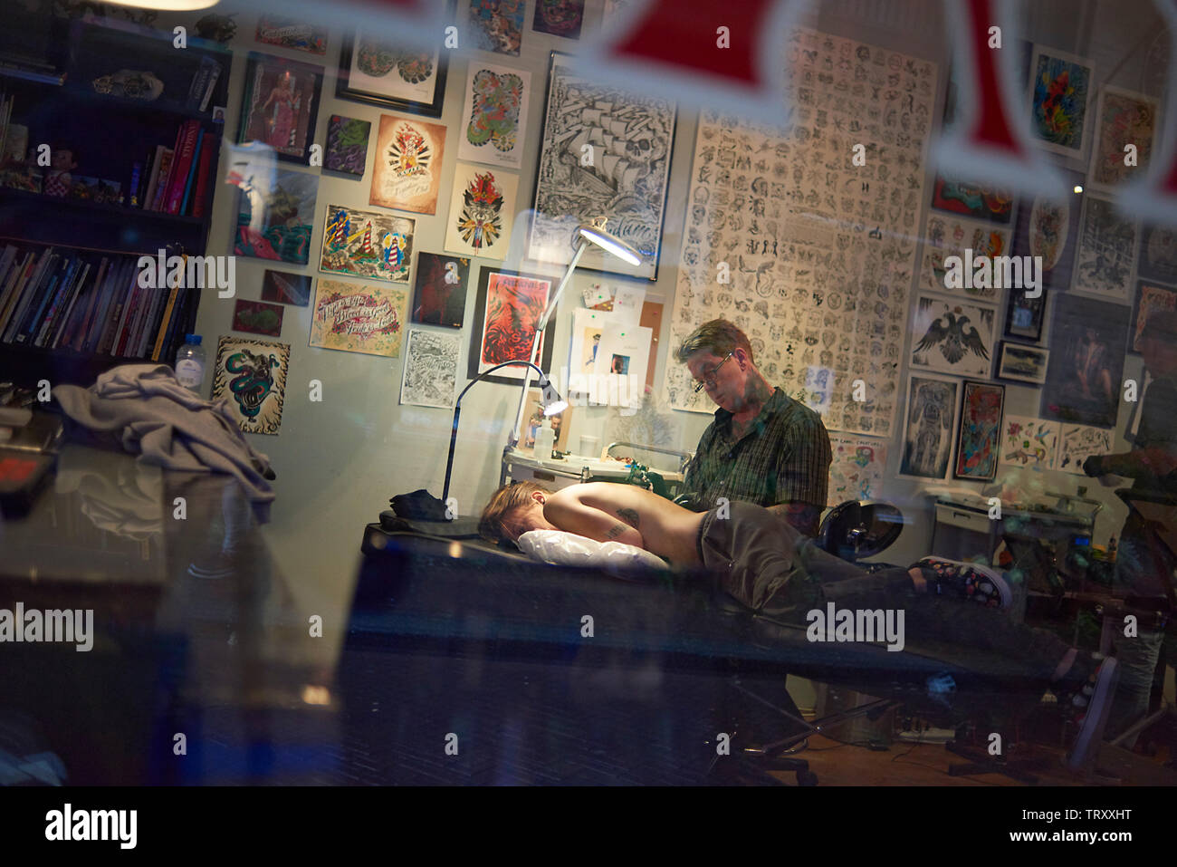 Tattoo artist tattooing the back of a woman in his shop in Amsterdam - Stock Image