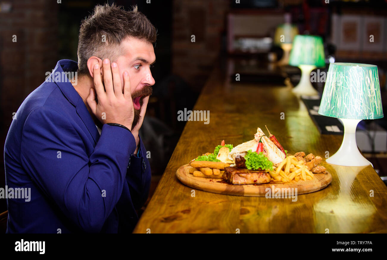 High calorie snack. Relax after hard working day. Businessman formal suit sit at bar counter. Man received meal with fried potato fish sticks meat and - Stock Image