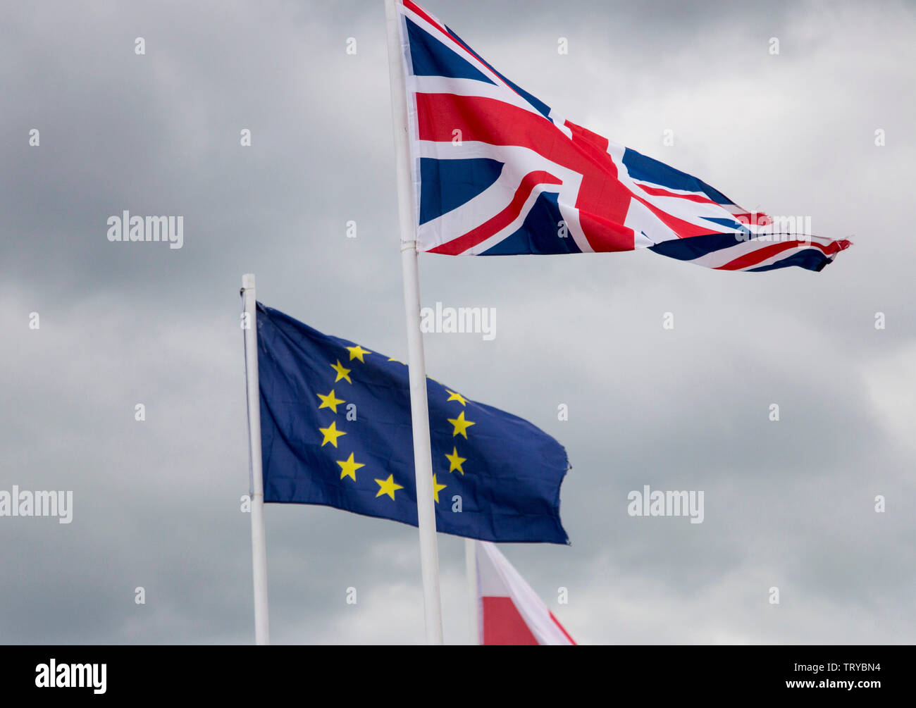 Union Jack and EU flags flying on masts - Stock Image