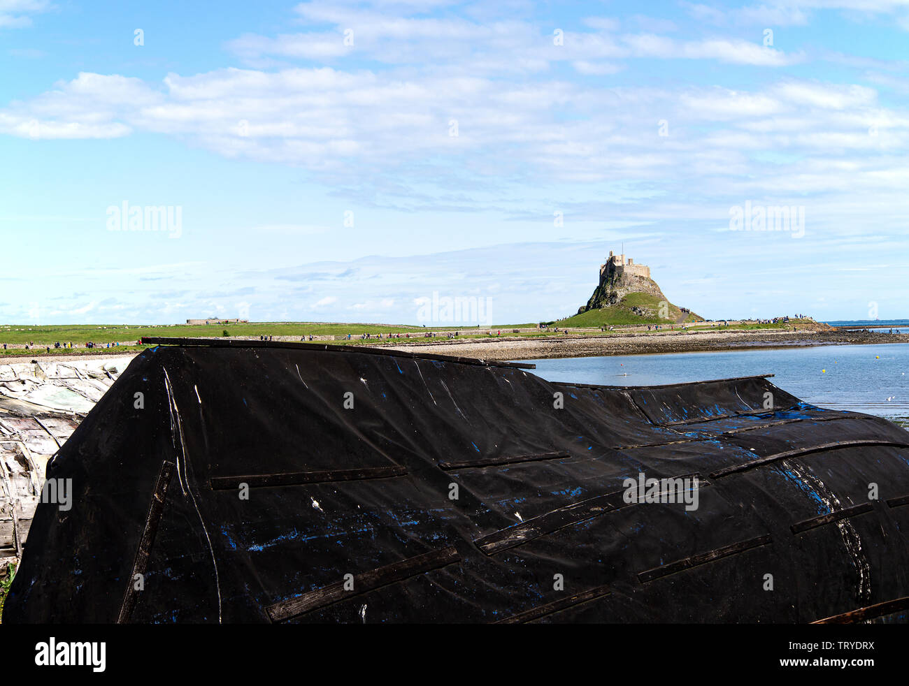 Old Upturned Fishing Boat Hulls Used as a Hut with Lindisfarne Castle on Holy Island Northumberland England United Kingdom UK Stock Photo