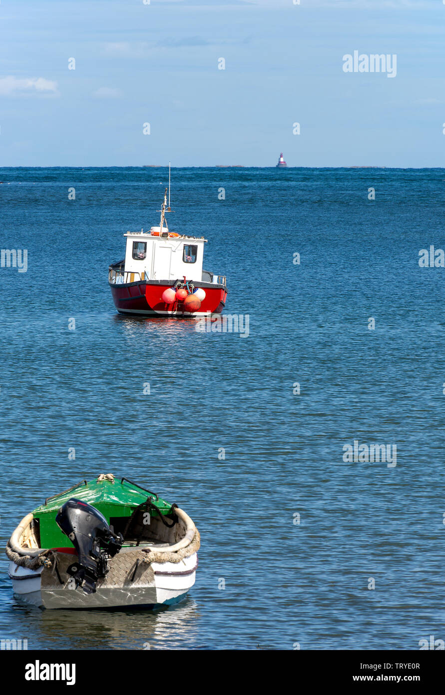 Fishing Boats Moored Off Holy Island in a Sheltered Bay with Longstone Lighthouse in the Background Northumberland England United Kingdom UK Stock Photo