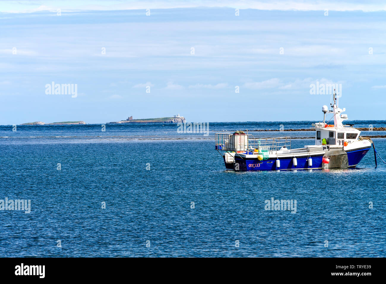 Fishing Boat Moored Off Holy Island in a Sheltered Bay with the Farne Islands in Background Northumberland England United Kingdom UK Stock Photo