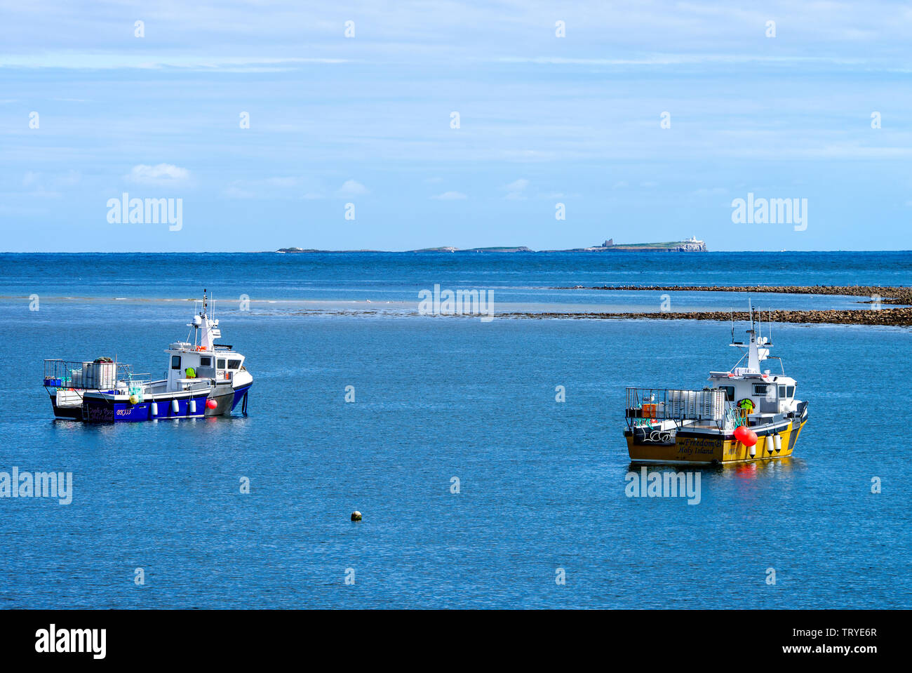 Fishing Boats Moored Off Holy Island in a Sheltered Bay with the Farne Islands in Background Northumberland England United Kingdom UK Stock Photo
