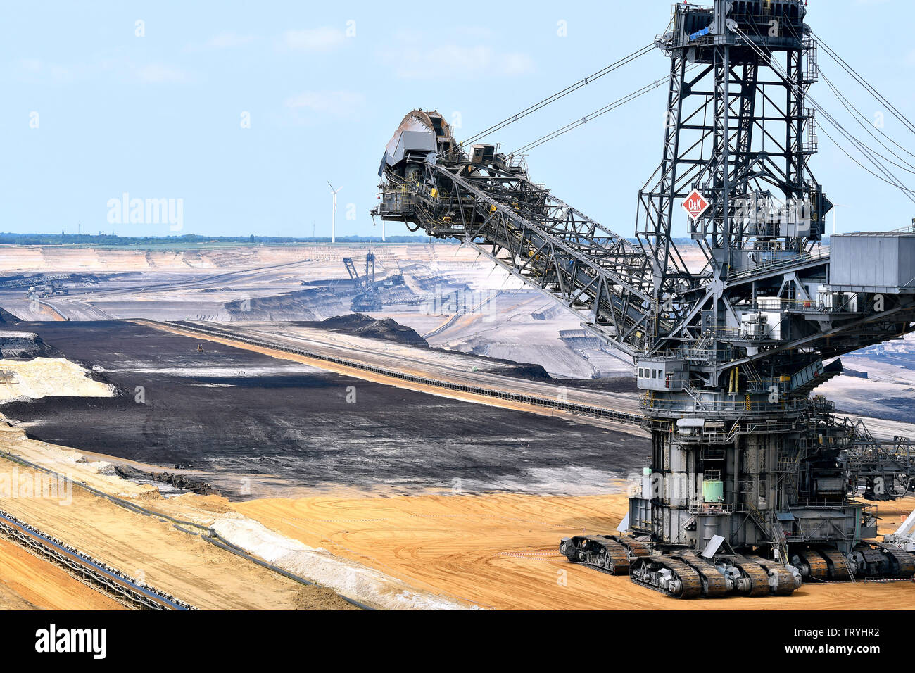 Bucket wheel excavator and wind turbines in the Garzweiler brown coal opencast mining in the Rhineland brown coal mining area. Stock Photo