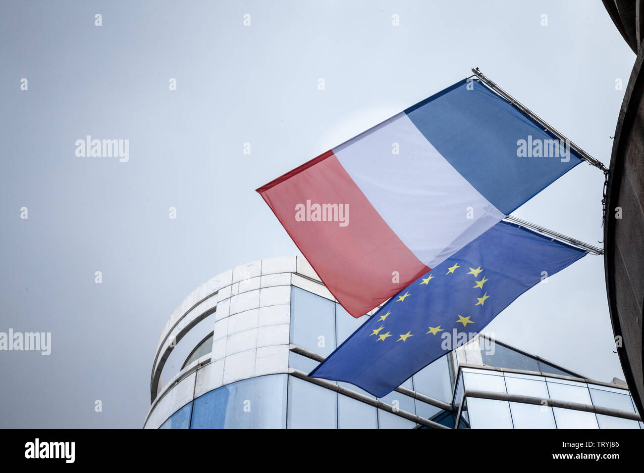 French flag and European Union flag standing in front of a business building, waiving. France is one of the main actors and members of the EU  Picture - Stock Image