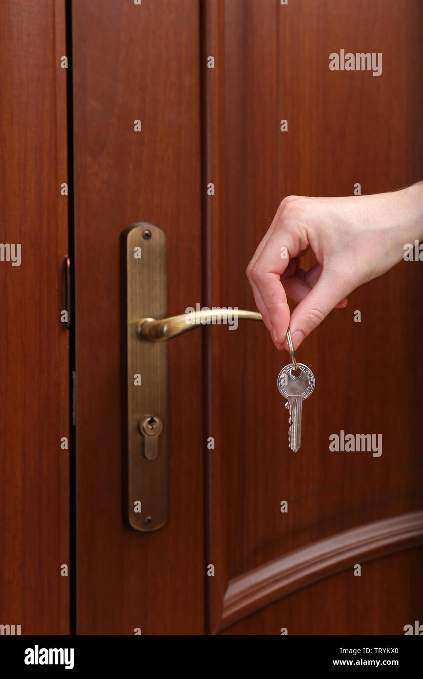 Locking up or unlocking door with key in hand Stock Photo